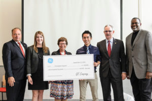 UW biomedical engineering undergraduate Chris Nguyen (center right) receives a GE Unimpossible Missions Award during a ceremony held in Engineering Hall at the University of Wisconsin-Madison on Sept. 12, 2016. Nguyen will receive a scholarship of up to $100,000 and a 10-week paid internship at the GE Global Research Center in Niskayuna, New York. (Photo by Bryce Richter / UW-Madison)
